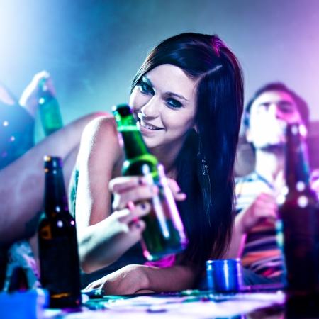 man drinkt bier: meisje bij drugs gevoed house party met bierfles.