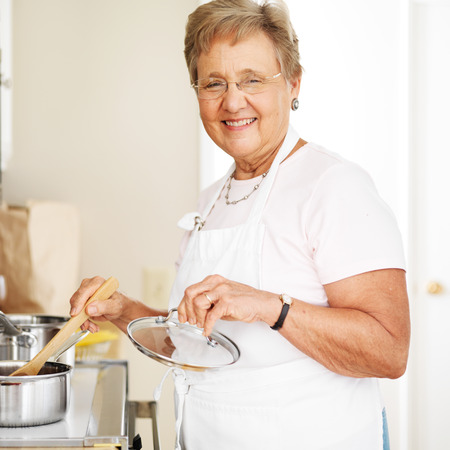 happy grandmother cooking in kitchen Фото со стока