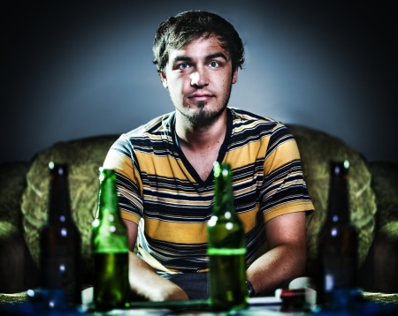 drunk young man on couch with beer photo
