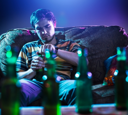 young man drinking beer alone photo