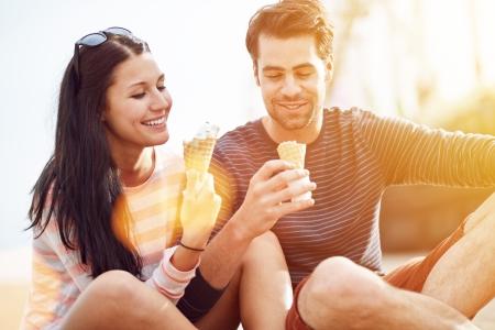 pareja comiendo: romántica pareja comer helado en el parque Foto de archivo