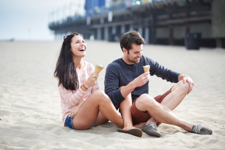 couple sitting in sand at sant monica pier. photo