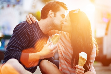 a couple: romantic couple kissing while holding ice cream