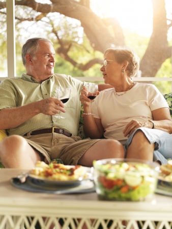 senior couple having dinner on patio photo