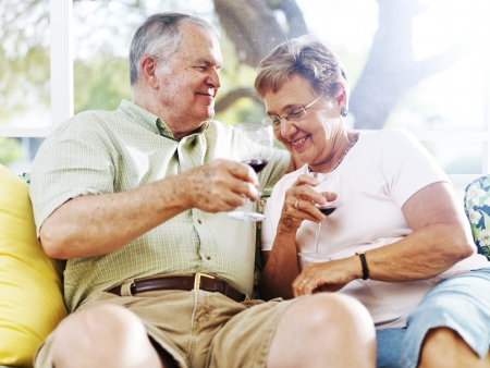 senior couple drinking wine outside on patio photo