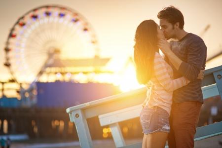 romantische paar kussen bij zonsondergang in de voorkant van Santa Monica reuzenrad