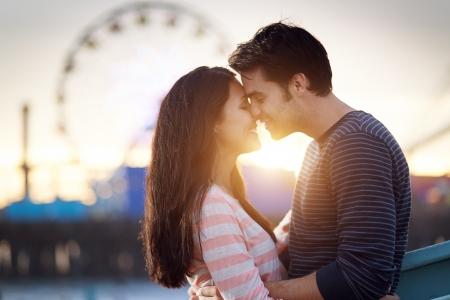 novios besandose: pareja rom�ntica en frente del parque de atracciones de Santa M�nica al atardecer