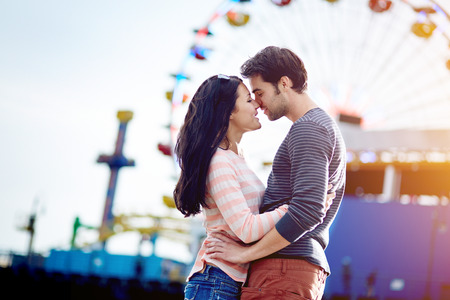 romantic couple embracing with santa monica pier in background