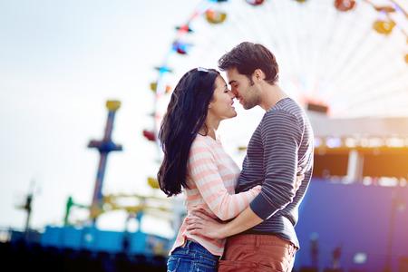 amusement park: romantic couple embracing with santa monica pier in background