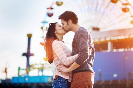 young couple kissing: romantic couple kissing in front of santa monica ferris wheel