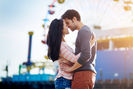 romantic couple kissing in front of santa monica ferris wheel photo
