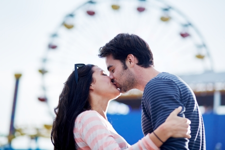 romantic couple kissing in front of santa monica ferris wheel