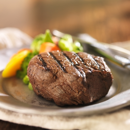 grilled steak on plate with vegetables photo