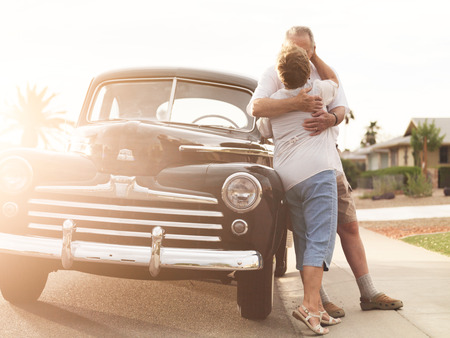 senior couple with vintage car kissing photo
