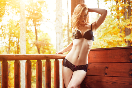 sexy redhead in bra and panties on cabin deck photo