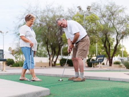 senior couple playing mini golf Фото со стока