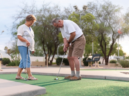 senior couple playing mini golf Stock Photo