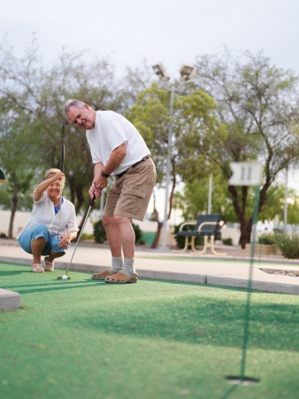 senior couple playing mini golf photo