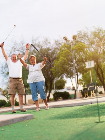 celebrating: senior couple playing mini gulf celebrating Stock Photo
