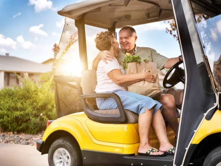 coming home: happy elderly couple coming home with groceries on golf cart