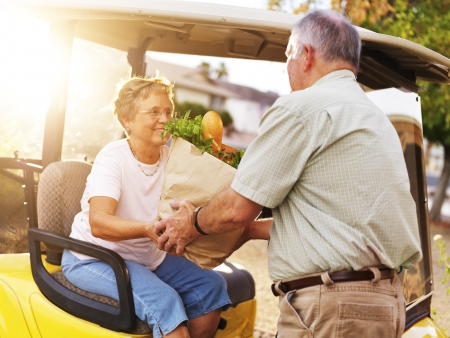 elderly couple bringing home groceries photo