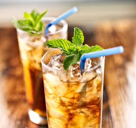 tall glass: iced sweet tea close up with blue straw Stock Photo