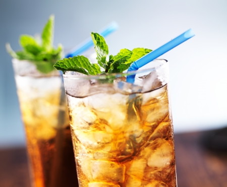 iced tea with blue straw and mint garnish photo