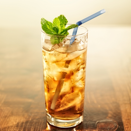 golden iced tea with blue straw and mint photo