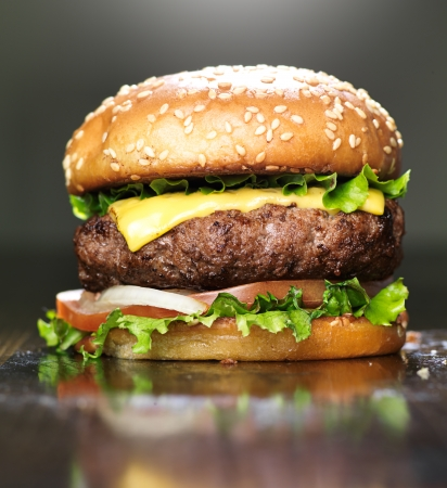 burger with melted cheese and sesame bun photo