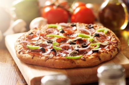 pizza italiana con pepperoni suprema y coberturas Foto de archivo