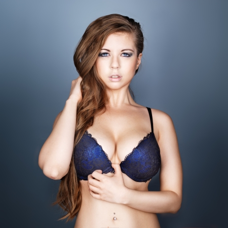 sexy girl in bra and long hair on dark blue background