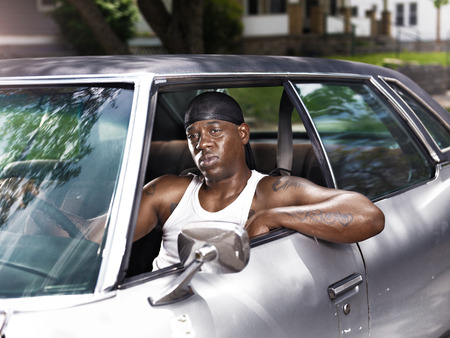 rusty car: cool african man in car wearing wife beater and dew rag Stock Photo