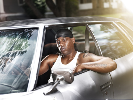beater: cool african man in car wearing wife beater and dew rag Stock Photo