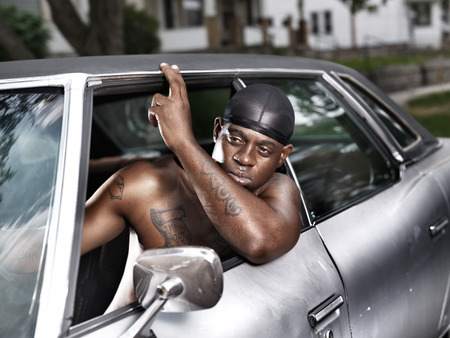 rusty car: rough african american in old car shirtless