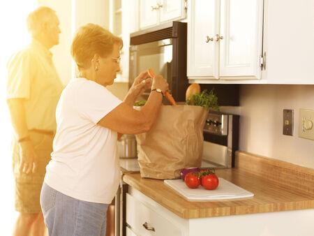 高齢者のカップルが自宅で食料品を片付けて 写真素材