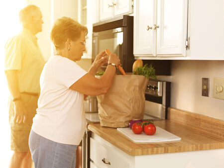 Elderly couple putting away groceries at home
