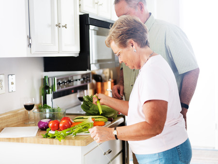senior couple preparing vegetables together photo