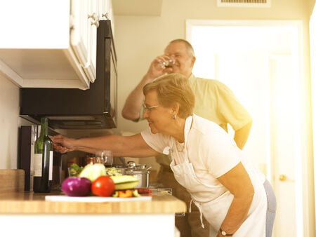 old couple making dinner together in kitchen photo