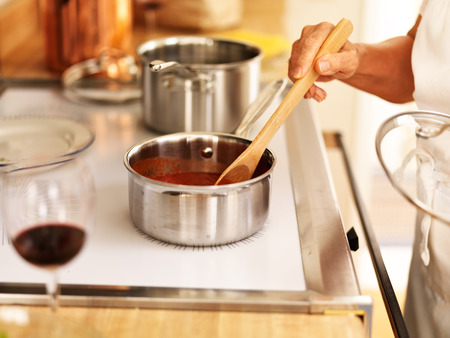 spaghetti saus: roeren van een kleine pot spaghettisaus op het fornuis Stockfoto