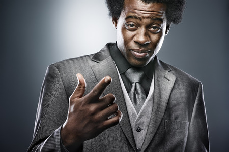 african man in suit gesturing with hand photo