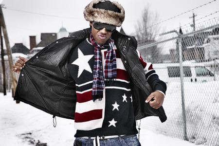 glass fence: funky african man in american flag themed winter clothing Stock Photo