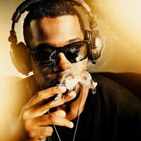 joven fumando: Hombre africano fresco fumar el uso de auriculares conjuntas