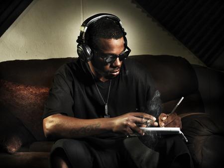 스튜디오에서 주 책에 가사를 쓰고 DJ가