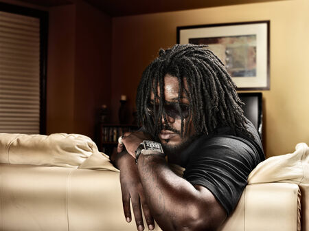 cool black man with dreads on leather couch. photo