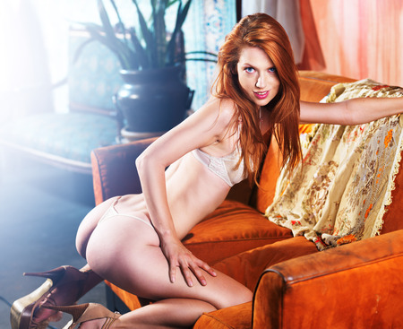 sexy petite red head posing on couch photo