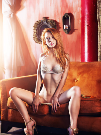sexy redhead in skimpy lingerie on couch Stock Photo