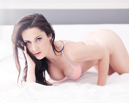 sexy blue eyed brunette posing on bed photo