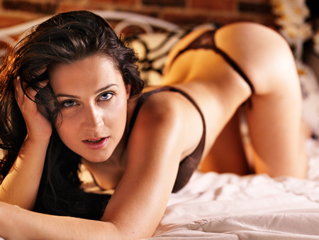sexy brunette on bed wearing thong photo