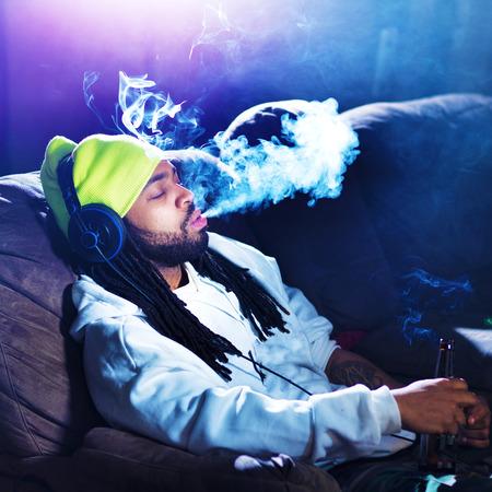 smoking marijuana: cool man smoking marijuana on his couch Stock Photo