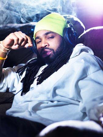 cool man smoking marijuana on his couch photo